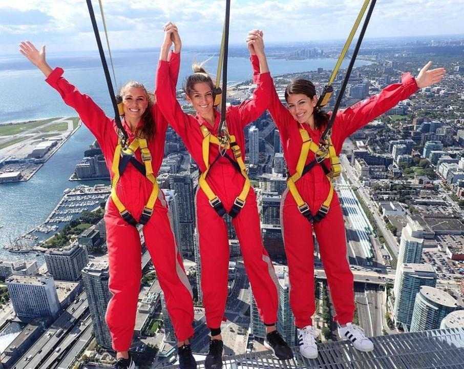Alex Morgan (sebelah kiri) bersama teman-temannya mendatangi CN Tower Edge Walk di Kanada. Tempat menguji nyali dengan berdiri di pinggiran gedung pencakar langit (@alexmorgan13/Instagram)