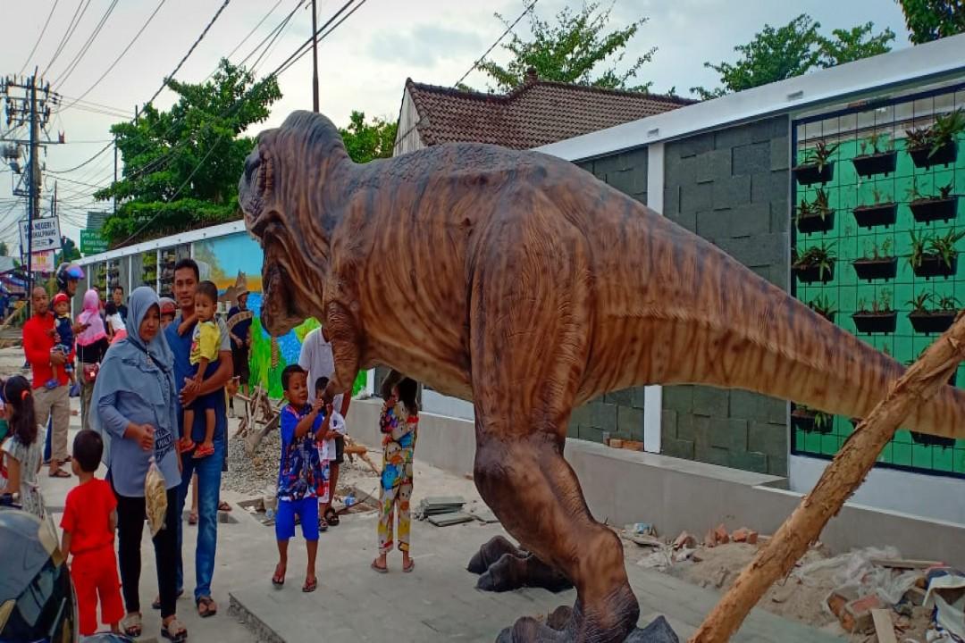Patung Dinosaurus atau hewan purbakala yang terletak di Simpang 7, Jalan Ahmad Yani, Kecamatan Taman Sari, Kota Pangkalpinang ramai dikunjungi warga.(foto: gusti/babelreview)