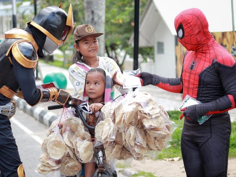 Dua orang pria yang berpakaian layaknya Super Hero sedang membagikan masker kepada dua orang anak yang berjualan kempelang keliling