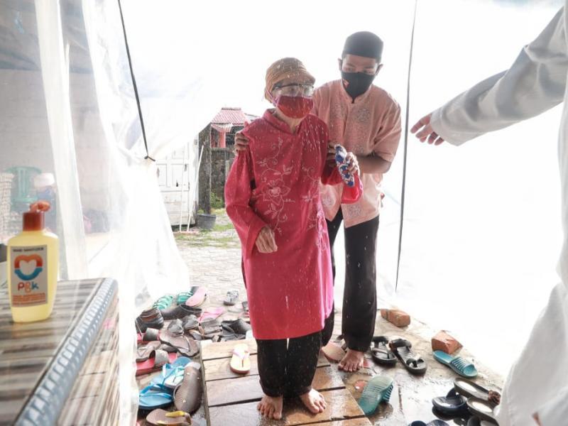 Salah seorang nenek sedang melewati bilik desinfektan sebelum memasuki area Masjid.