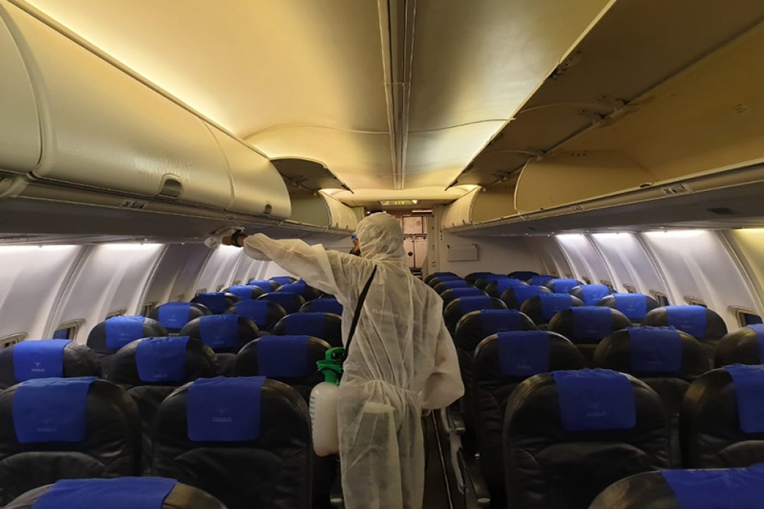 Petugas sedang melakukan penyemprotan disinfektan di Dalam kabin pesawat milik Sriwijaya Air Group. Foto: Ist